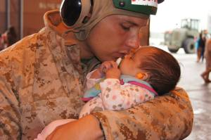 Captain Lee Jones embraces his three week old daughter, Skylar, prior to embarking on an eight month deployment to Afghanistan as part of the U.S. Marine Corps. Jones, now stationed at U.S. Marine Corps Air Station Miramar, will soon transition into non-military life and is a recent applicant of UC San Diego Extension and its project management certificate offered in conjunction with the online master's option through the University of Wisconsin.